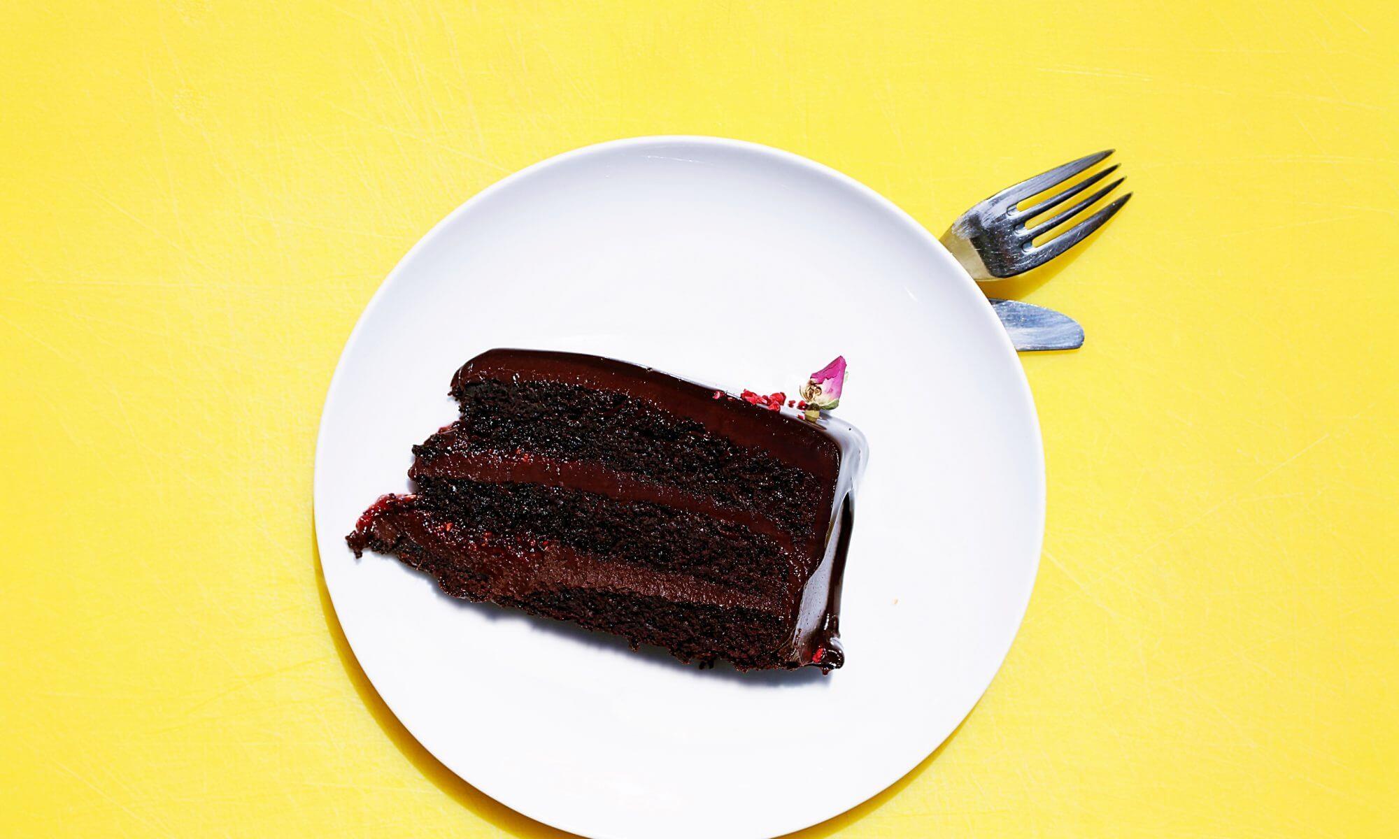 Schokoladen Kuchen auf weißem Teller auf gelben Tisch