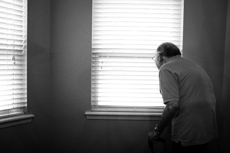 Opa in Einsamkeit mit Blick aus dem Fenster