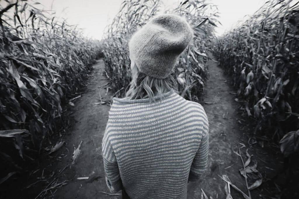 Frau vor zwei Feldwegen und vor der Entscheidung