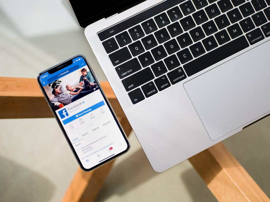 Laptop neben Handy mit einem Netzwerk für Gruppen geöffnet