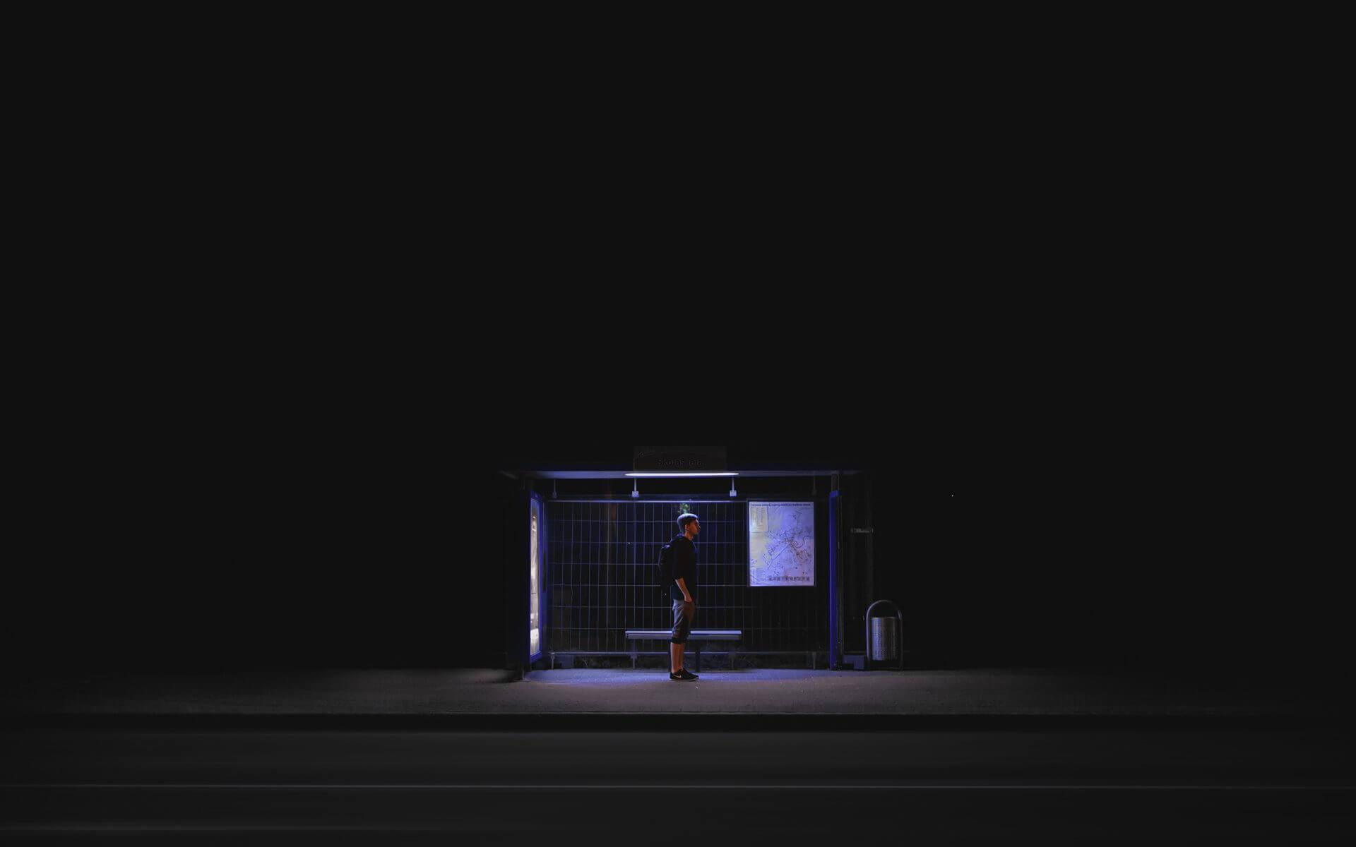 Individuum alleine an Bushaltestelle in der Nacht