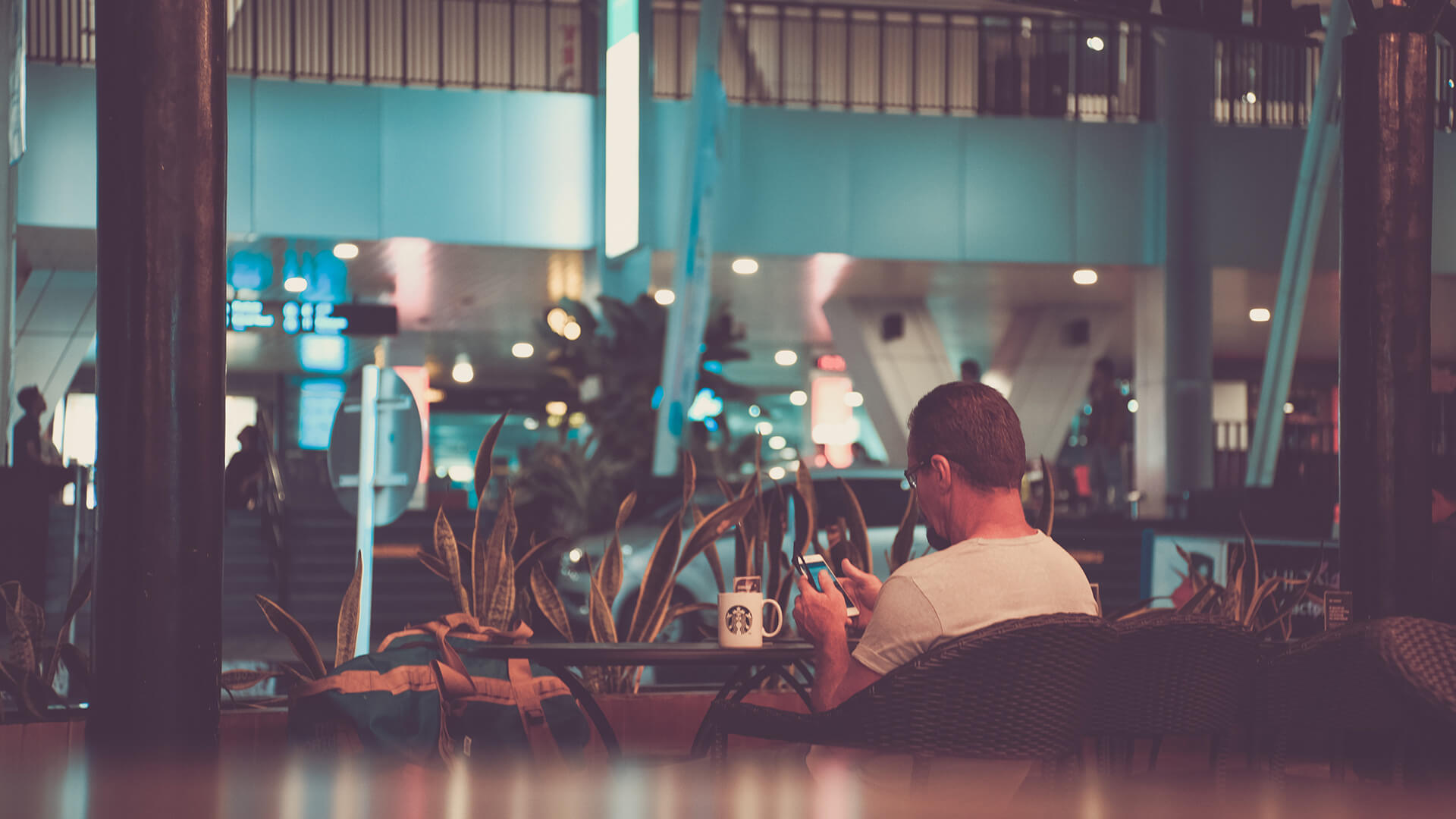Person alleine sitzend vertieft ins Smartphone